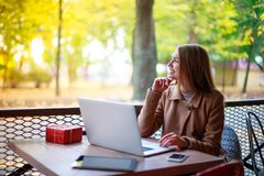 Young girl in a cafe with a laptop, phone and tablet Royalty Free Stock Photos