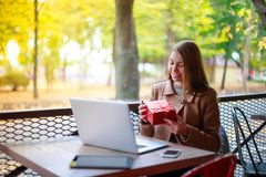 Young, girl in outdoor cafe with laptop shows her gift through video call, Aipi telephony Stock Photo
