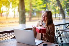 Young, girl in outdoor cafe with laptop shows her gift through video call, Aipi telephony Stock Photos