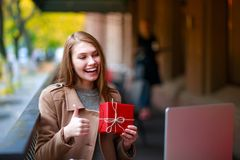 Young, girl in outdoor cafe with laptop shows her gift through video call, Aipi telephony Stock Images