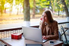 A young, cheerful girl in an outdoor cafe on a tree background sits at a table with a laptop and gift box. Stock Photo