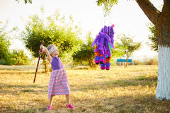 Young girl at an outdoor party hitting a pinata. Celebrating a birthday Stock Images