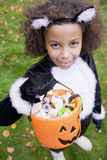 Young girl outdoors in cat costume holding candy. Young girl outdoors in cat costume on Halloween holding candy looking at camera stock photo