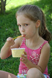 Young girl outdoors eating ice cream Stock Photography