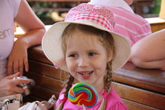 Young girl outdoors eating lollipop Royalty Free Stock Images