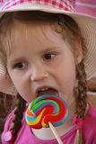 Young girl outdoors eating lollipop Stock Image