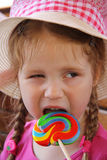 Young girl outdoors eating lollipop Royalty Free Stock Photography