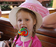 Young girl outdoors eating lollipop Stock Images