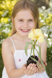 Young girl outdoors holding flower smiling Stock Photography