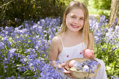 Young girl outdoors holding various eggs in basket Stock Photo