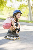 Young girl outdoors on i line skates smiling Stock Photography