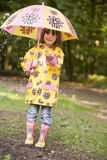 Young girl outdoors in rain with umbrella smiling. At camera Stock Images