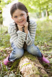 Young girl outdoors in woods sitting on log Stock Images