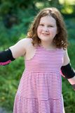 Young girl outside learning to riding on roller skates on driveway wearing protective elbow, wrist and knee pads. View of Young girl outside learning to riding Stock Image