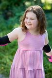Young girl outside learning to riding on roller skates on driveway wearing protective elbow, wrist and knee pads. View of Young girl outside learning to riding Royalty Free Stock Photography