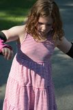 Young girl outside learning to riding on roller skates on driveway wearing protective elbow, wrist and knee pads. View of Young girl outside learning to riding Stock Images