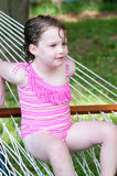 Young girl outside in swimming suit sitting on hammock. View of Young girl outside in swimming suit sitting on hammock royalty free stock image