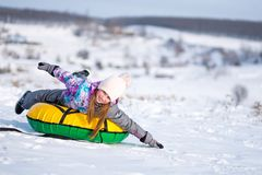 Little girl enjoying snow tubing at sunny weather. Young girl outstretched her arms while enjoying snow tubing at sunny winter weather stock image