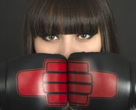 Young girl over black background with boxing gloves Stock Images