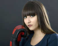 Young girl over black background with boxing gloves Royalty Free Stock Photos