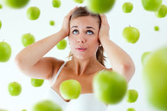 Young girl overwhelmed by diet, surrounded by apples. Royalty Free Stock Photography