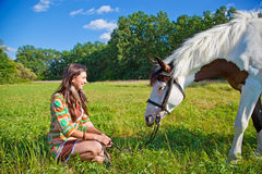 A young girl with a paint horse. A young girl dressed as an Indian walking with a paint horse royalty free stock images
