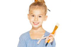 Young girl - painter. Little girl painter in a blue dress with paints and brushes Stock Photo