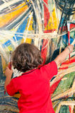 Young Girl with Painting. Young girl with brushes in her hand looks at an abstract painting royalty free stock photo