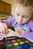 Young girl painting. Five year old female with water color paints Royalty Free Stock Photography