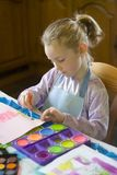 Young girl painting. Female child painting with watercolors at the kitchen table Royalty Free Stock Photography