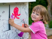 Young Girl Painting Cardboard House royalty free stock photos