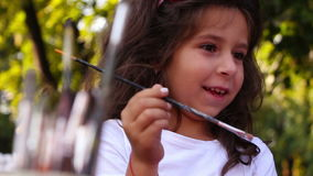 Young girl painting on a ceramic figure stock video footage