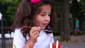 Young girl painting on a ceramic figure stock footage