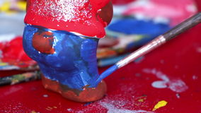 Young girl painting on a ceramic figure stock video