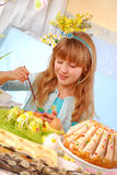 Young girl  painting easter eggs. Young girl painting easter eggs by the table Stock Photo