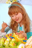 Young girl  painting easter eggs. Young girl painting easter eggs by the table Royalty Free Stock Photography