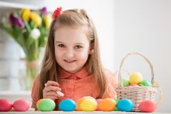 Young girl painting eggs by the desk, smiling. Easter eggs. Christian traditions Stock Image