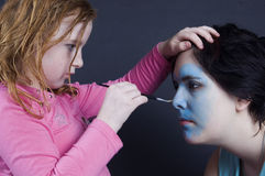 Young girl is painting females face Royalty Free Stock Photo