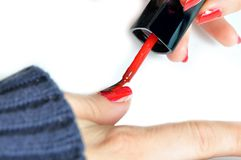 Young girl painting her nails red Stock Photos