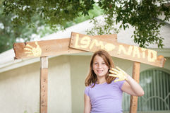 Young girl painting a lemonade stand sign Stock Photos