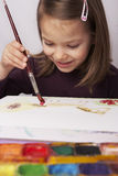 Young girl painting picture. Happy smiling young girl holding a brush and painting picture stock images