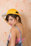 Young girl painting wall. Young caucasian brunette girl painting wall Royalty Free Stock Photos