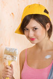 Young girl painting wall. Young caucasian girl painting wall indoors Stock Image