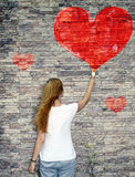 A young girl, painting, watercolor krsnoe heart. On the stone wall, the concept of love Royalty Free Stock Photos