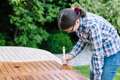 Free Young Girl Painting Wooden Exotic Wood Table In The Garden With A Brush - Shallow Depth Of Field Stock Images - 212683164