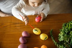 A young girl is painting on a yellow easter egg with her right hand while holding a red easter egg in her left hand. A young girl is painting on a yellow easter royalty free stock photos
