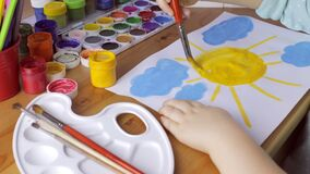 Young girl painting a yellow sun on white paper stock footage