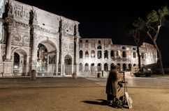 A young Girl Paints the Arch of Constantine and the Colosseum at. Night Royalty Free Stock Photo