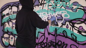 Young girl paints a graffiti on the wall stock video footage
