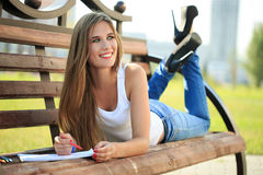 Young girl paints in a park sitting on a bench. Young beautiful girl paints in a park sitting on a bench royalty free stock photography